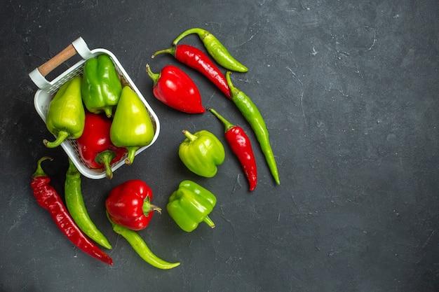 Bovenaanzicht groene en rode paprika's in plastic mand hete pepers op donkere ondergrond vrije plaats