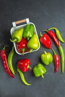 Bovenaanzicht groene en rode paprika's in plastic mand hete pepers op donkere ondergrond