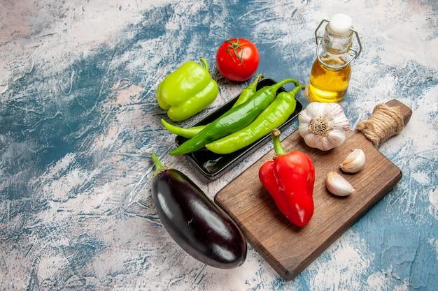 Bovenaanzicht groene hete pepers op zwarte plaat tomaat paprika knoflook op snijplank aubergine op blauw-witte achtergrond