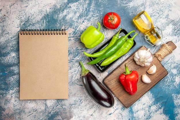 Bovenaanzicht groene hete pepers op zwarte plaat tomaat rode en groene paprika's knoflook op snijplank aubergine een notitieboekje op blauw-witte achtergrond