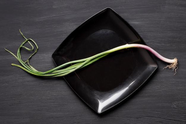 Bovenaanzicht groene knoflook op zwarte plaat
