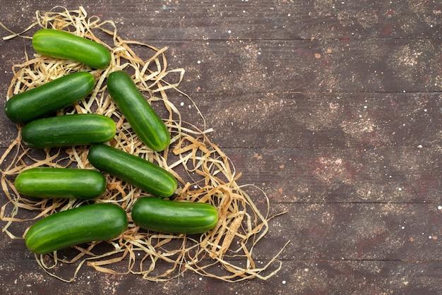Bovenaanzicht groene komkommers vers en rijp op bruin