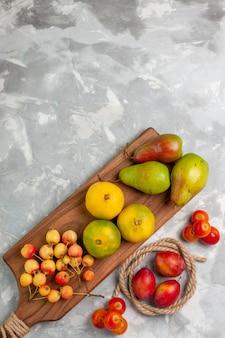 Bovenaanzicht groene mandarijnen met zoete kersen, pruimen en peren op het licht witte bureau.