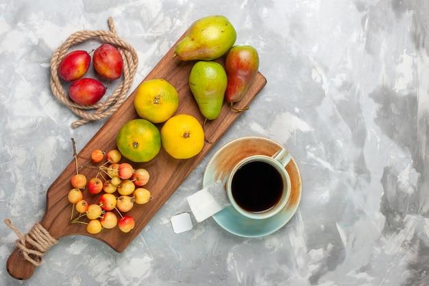 Bovenaanzicht groene mandarijnen met zoete kersen, pruimen en peren op lichte witte vloer.