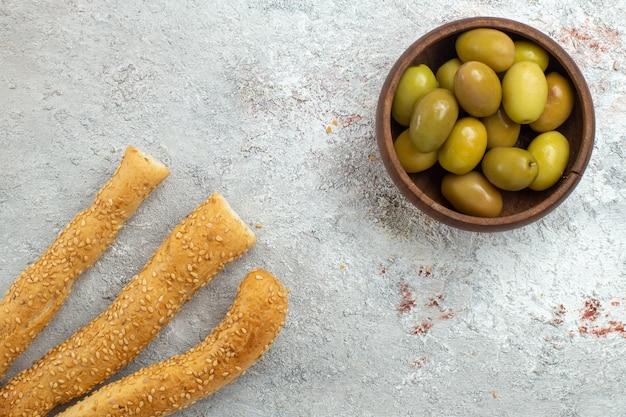 Bovenaanzicht groene olijven met broodbroodjes op witte ruimte