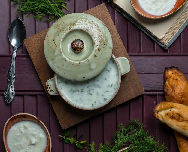 Bovenaanzicht groene pan met yoghurt binnen soep