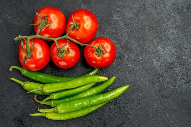 Bovenaanzicht groene pittige paprika's met rode tomaten