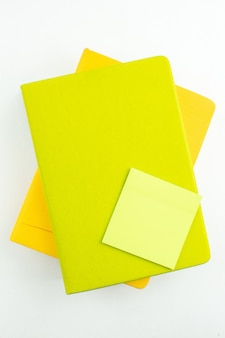 Bovenaanzicht groene plaknotitie op kleurrijke notebooks op witte tafel