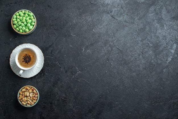 Bovenaanzicht groene snoepjes met kopje koffie en noten op de grijze achtergrond koekje suiker cake zoete koekje