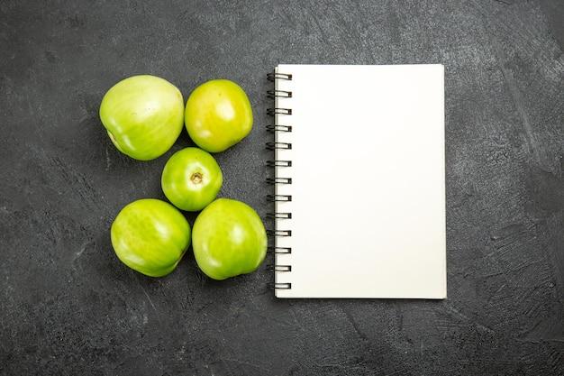 Bovenaanzicht groene tomaten een notitieboekje op een donkere ondergrond