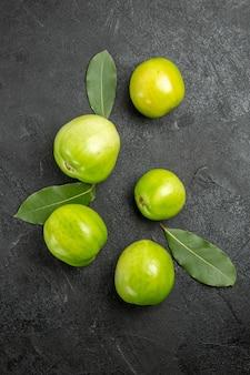 Bovenaanzicht groene tomaten en laurierblaadjes op donkere ondergrond