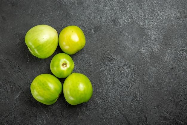 Bovenaanzicht groene tomaten op donkere ondergrond
