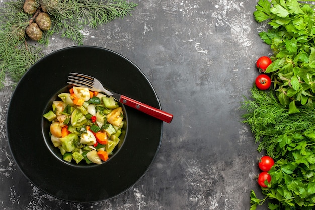 Bovenaanzicht groene tomatensalade een vork op ovale plaat greens tometoes op donkere achtergrond