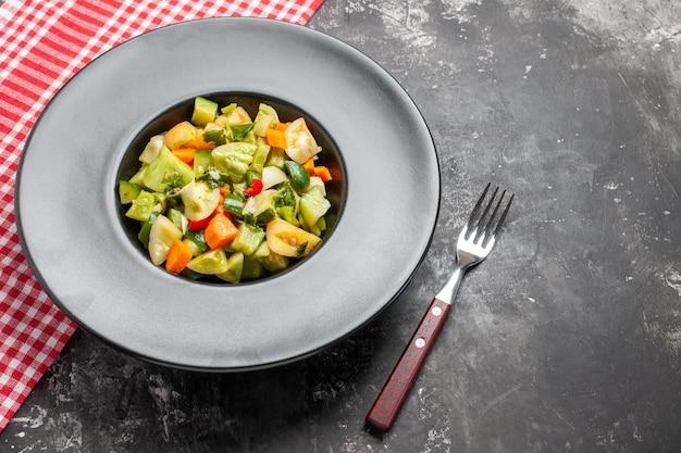 Bovenaanzicht groene tomatensalade op grijze ovale plaat een vork op donkere achtergrond