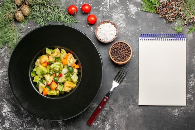 Bovenaanzicht groene tomatensalade op ovale plaat een vork notitieblok kruiden op donkere achtergrond