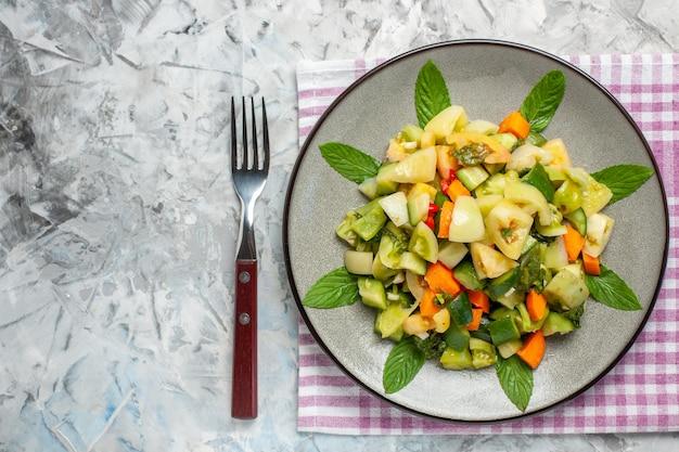 Bovenaanzicht groene tomatensalade op ovale plaat een vork op donkere achtergrond