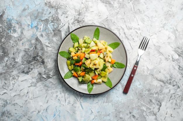 Bovenaanzicht groene tomatensalade op ovale plaat een vork op grijze achtergrond