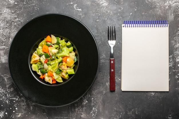 Bovenaanzicht groene tomatensalade op ovale plaat een vorknotitieboekje op donkere achtergrond