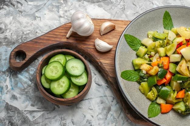 Bovenaanzicht groene tomatensalade op ovale plaat knoflook op snijplankkom met gesneden komkommers op donkere achtergrond
