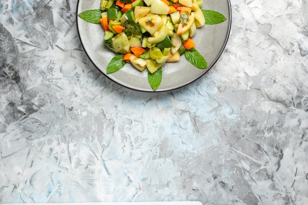 Bovenaanzicht groene tomatensalade op ovale plaat op grijze achtergrond