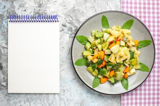 Bovenaanzicht groene tomatensalade op ovale plaat roze tafelkleed een notitieboekje op grijze achtergrond
