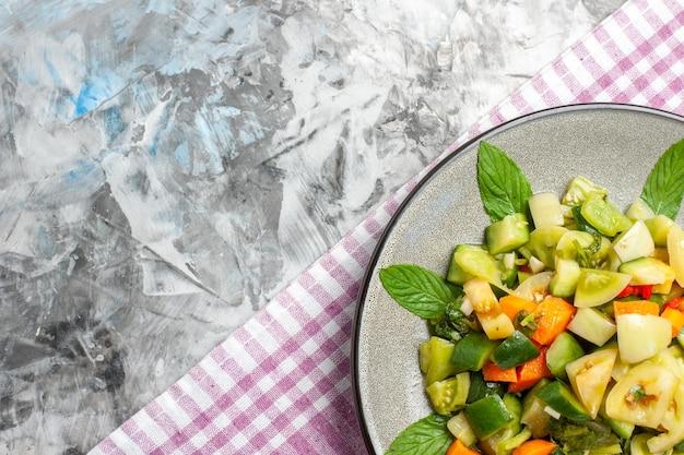 Bovenaanzicht groene tomatensalade op ovale plaat roze tafelkleed op grijs oppervlak