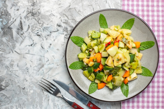 Bovenaanzicht groene tomatensalade op ovale plaat roze tafelkleed vork op grijs oppervlak