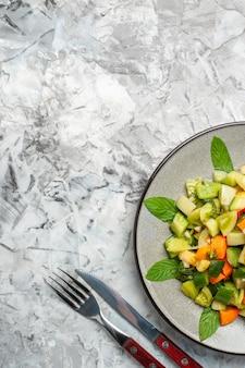 Bovenaanzicht groene tomatensalade op ovale plaatvork en mes op grijze achtergrond