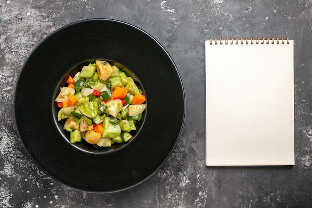 Bovenaanzicht groene tomatensalade op zwarte ovale plaat kladblok op donkere achtergrond