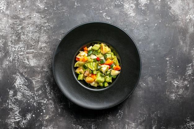 Bovenaanzicht groene tomatensalade op zwarte ovale plaat op donkere achtergrond
