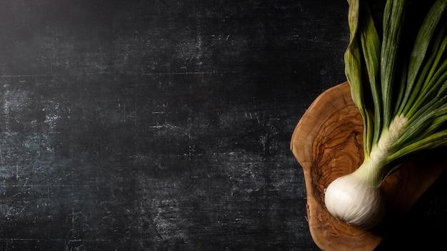 Bovenaanzicht groene ui op snijplank met kopie-ruimte
