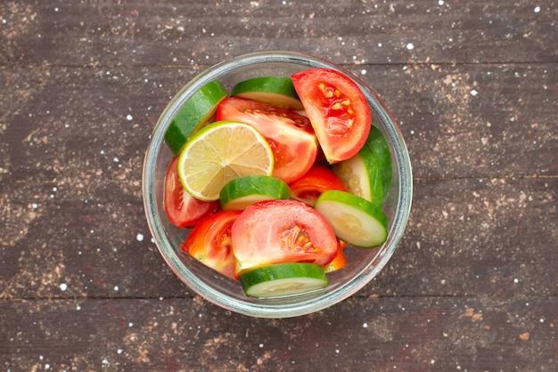 Bovenaanzicht groente salade met gesneden komkommers tomaten en citroen op bruin, groentesap citroen eten salade