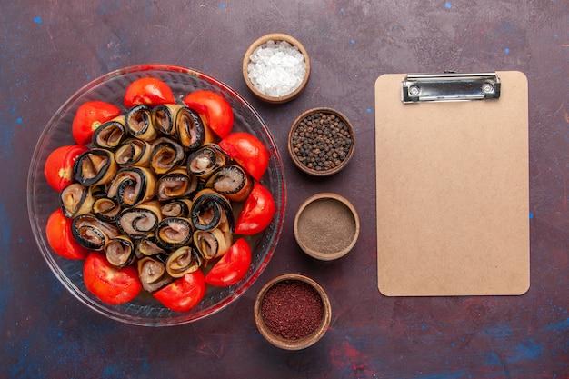 Bovenaanzicht groentemeel gesneden en gerolde tomaten met aubergines en kruiden op de donkere achtergrond