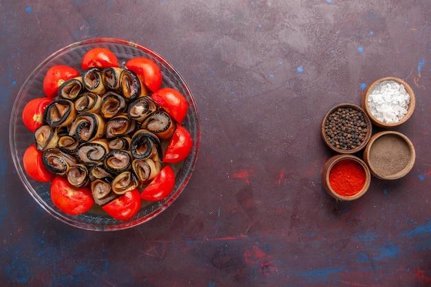 Bovenaanzicht groentemeel gesneden en gerolde tomaten met aubergines en kruiden op donkerpaars bureau