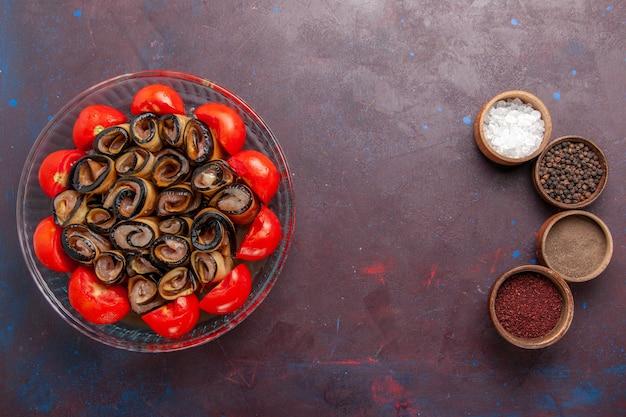 Bovenaanzicht groentemeel gesneden en gerolde tomaten met aubergines en kruiden op donkerpaarse achtergrond