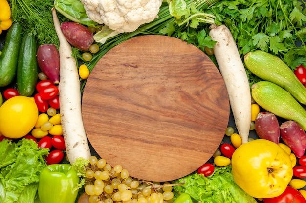 Bovenaanzicht groenten en fruit cherrytomaatjes cumcuat sla kweepeer druif citroen bloemkool witte radijs peterselie courgette komkommers ronde houten bord in het midden