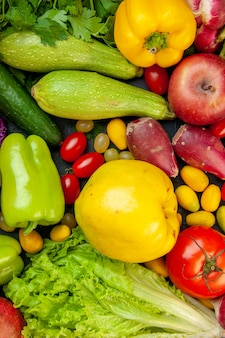 Bovenaanzicht groenten en fruit courgette paprika cherry tomaten cumcuat appel kweepeer komkommersla