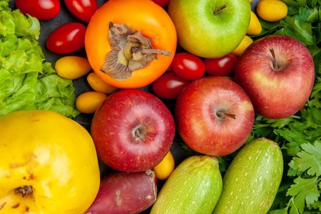 Bovenaanzicht groenten en fruit kerstomaatjes cumcuat appels sla kweepeer persimmon peterselie courgette
