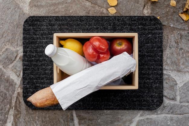 Bovenaanzicht groenten en melkfles in doos