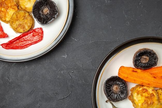 Bovenaanzicht groenten geroosterde champignons peper wortel op de borden op tafel