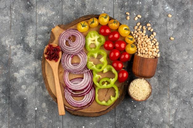 Bovenaanzicht groenten gesneden uien groene paprika hele rode en gele tomaten op het bruine bureau op de grijze vloer