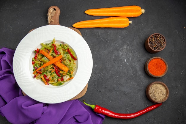 Bovenaanzicht groenten salade op de snijplank kruiden wortelen tafelkleed