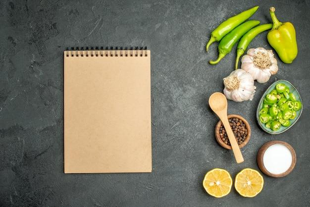 Bovenaanzicht groenten samenstelling pepers citroen en knoflook op donkere achtergrond