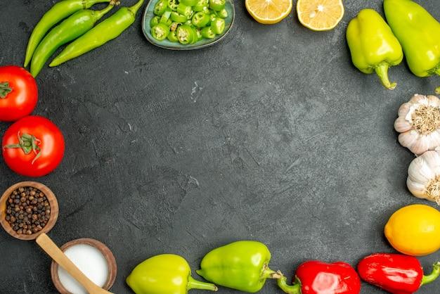 Bovenaanzicht groenten samenstelling tomaten paprika, citroen en knoflook op een donkere achtergrond