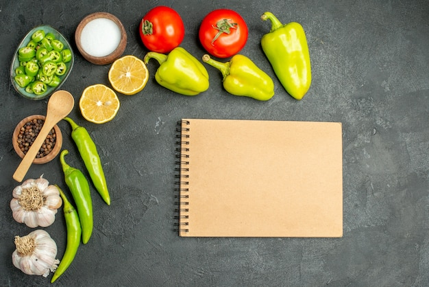 Bovenaanzicht groenten samenstelling tomaten paprika en knoflook op donkere achtergrond