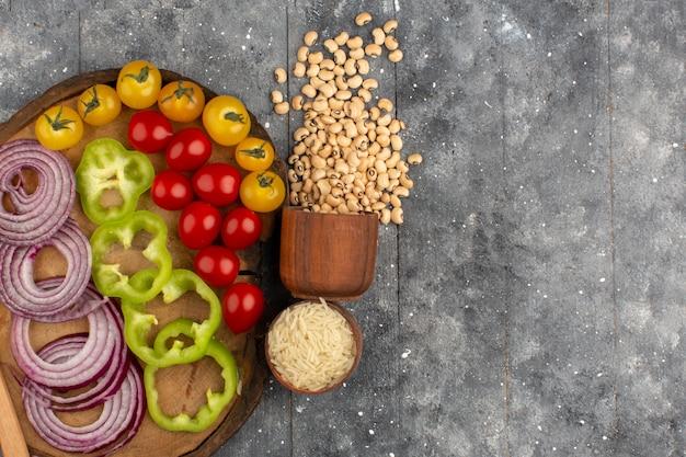 Bovenaanzicht groenten vers gesneden en geheel op het bruine bureau en de grijze achtergrond
