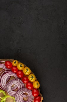 Bovenaanzicht groenten zoals uien, tomaten op de donkere vloer