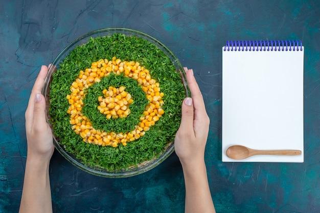 Bovenaanzicht groentensalade met likdoorns in ronde glazen plaat op het donkerblauwe bureau.