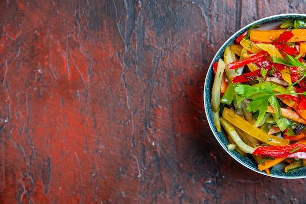 Bovenaanzicht groentesalade in kom op donkerrode tafel met vrije plaats