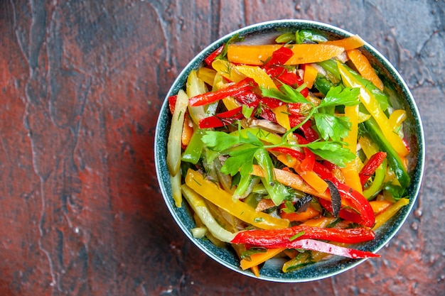 Bovenaanzicht groentesalade in kom op donkerrode tafel